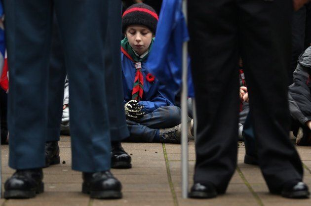 A young boy joins in a moment of silence during the Remembrance Day ceremony at Veterans Memorial