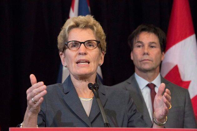 Ontario Premier Kathleen Wynne speaks as Health Minister Eric Hoskins looks on in Toronto on Oct. 20,