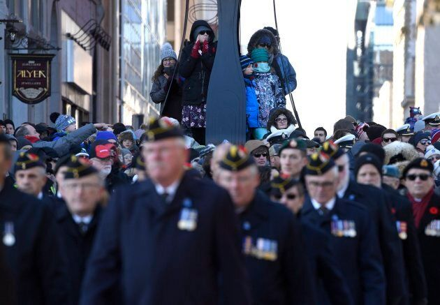 People climb a lamp post to get a better view as veterans march during the National Remembrance Day Ceremony...