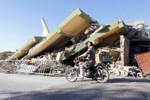 A man rides a motorcycle past a damaged building following an earthquake in the town of Darbandikhan,...