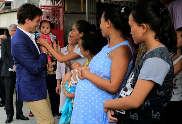 Prime Minister Justin Trudeau carries a baby during his visit at a non-governmental organization in Manila, Philippines, Nov. 12, 2017.