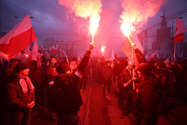Protesters light flares and carry Polish flags during a rally, organised by far-right, nationalist groups,...