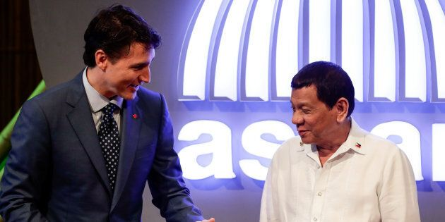Prime Minister Justin Trudeau talks to Philippine President Rodrigo Duterte before the opening ceremony...