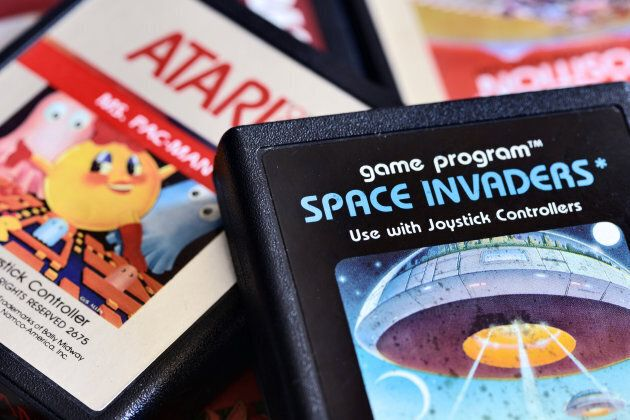 Close-up photos of vintage Atari 2600 video game cartridges including Space Invaders, Mrs Pac-Man, Pole Position and Kangaroo.