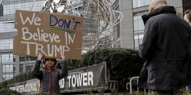A boy stands with a sign protesting against U.S. Republican presidential candidate Donald Trump, outside...