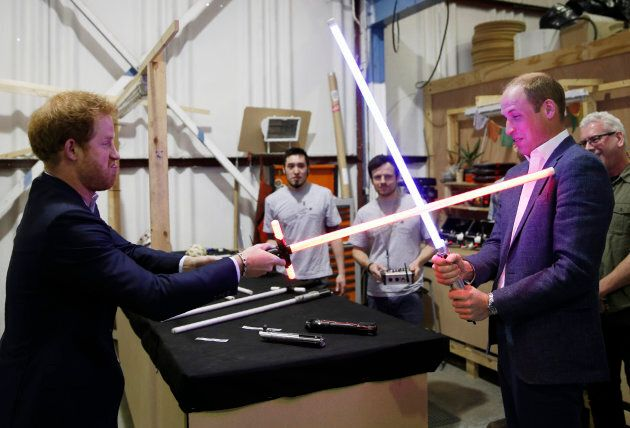 Prince Harry and Prince William try out lightsabers during a tour of the Star Wars sets at Pinewood studios...