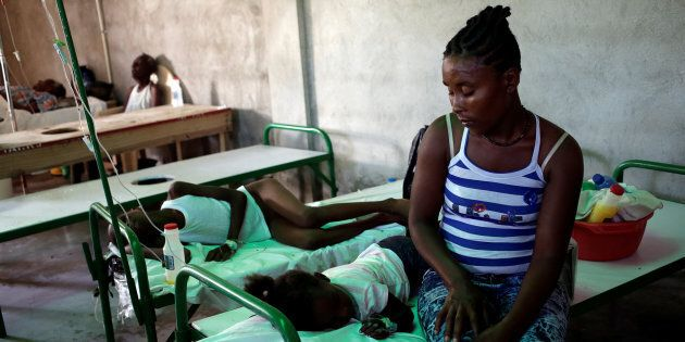 A woman sits next to her daughter as she receives treatment for cholera at the Immaculate Conception...