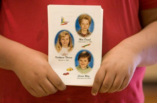 A mourner holds a program showing the pictures of Max, Kaitlynne and Cordon Schoenborn during a public...