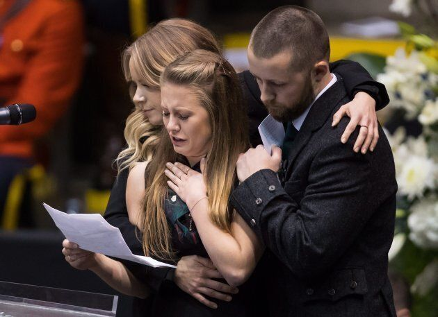 Fay Davidson, front left, is comforted by her sister Dina and brother Drew while speaking about their...