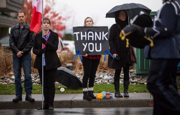 A woman holds a sign while the funeral procession carrying the body of Abbotsford Police Const. John...
