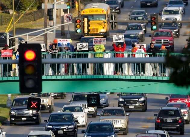Opponents of the Keystone XL pipeline demonstrate on the Dodge Street pedestrian bridge during rush hour...