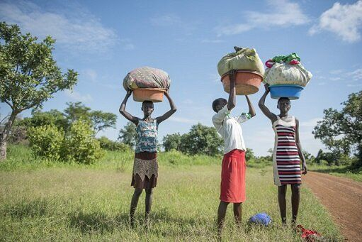School-age girls in South Sudan carry heavy loads of washing to the river. Their household responsibilities impact their ability to attend school.