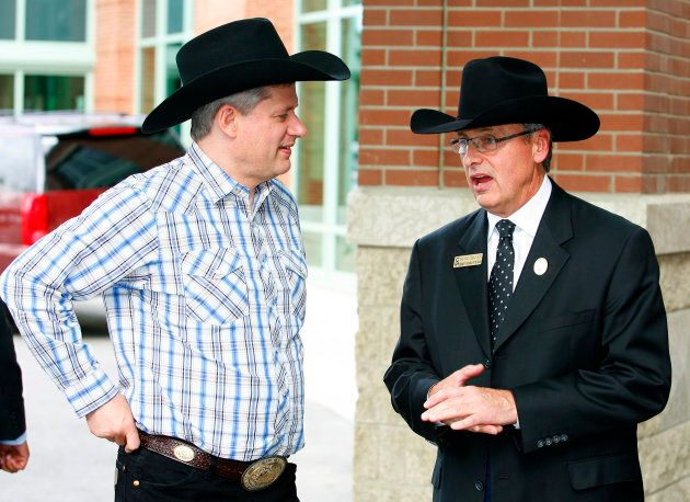 Canadian Prime Minister Stephen Harper (L) is greeted by Stampede president David Chalack during the...