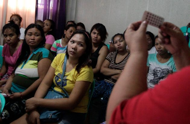 Women listen during a family planning lecture by a Likhaan NGO health worker at a reproductive health...