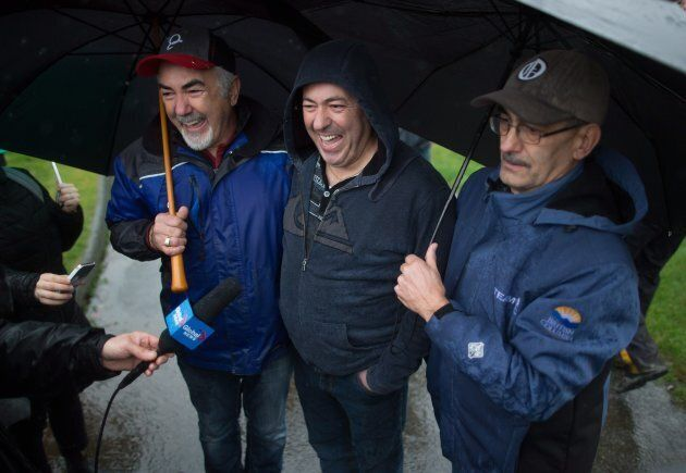 Annette Poitras' husband Marcel Poitras, centre, smiles while standing with his brothers Gerry, left,...