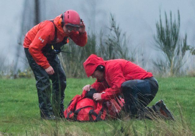 Search and rescue members check on Annette Poitras after she was rescued with a helicopter and a long...