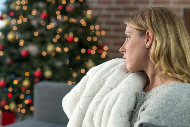 A woman is having a lonely Christmas by herself. She sits alone and looks sad as she is all alone on...
