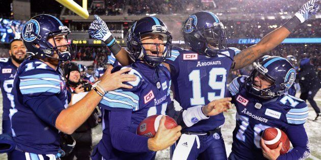 Toronto Argonauts quarterback Ricky Ray celebrates with teammates after defeating the Calgary Stampeders...