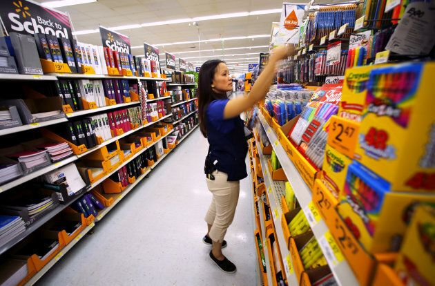 Walmart department manager Karren Gomes helps stock shelves with school supplies as the retail store...