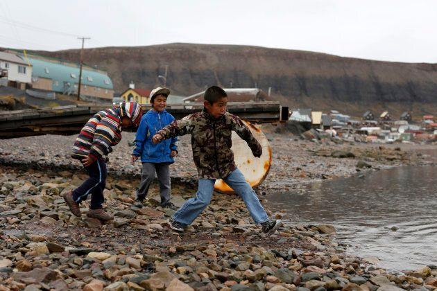 Young boys skip stones in the Arctic community of Arctic Bay in Nunavut.