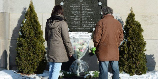 People stop at the memorial plaque in honour of the 13 students and one staff member killed in the Polytechnique...