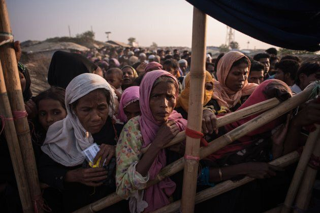 Rohingya Muslim refugees wait to be called to recieve food aid of rice, water and cooking oil in a relief...