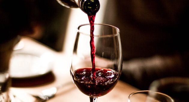 Red wine being poured into a stem glass at the