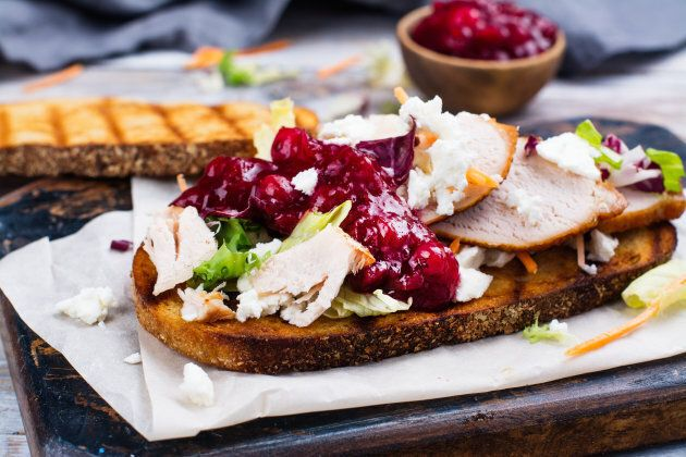 Homemade leftover thanksgiving day sandwich with turkey, cranberry sauce, feta cheese and