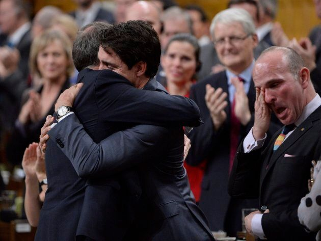 Prime Minister Justin Trudeau hugs Liberal MP Rob Oliphant as Liberal MP Randy Boissonnault (right) wipes...