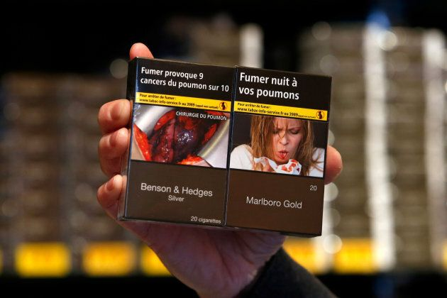 A tobacconist in France displays new plain packaging cigarettes wit health warnings on Jan. 2,