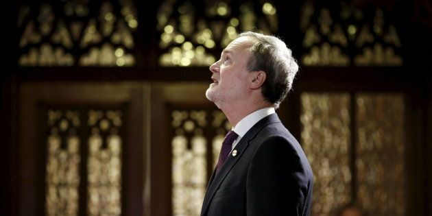 Andre Pratte looks up while waiting in the entrance of the Senate chamber before being sworn-in as a...