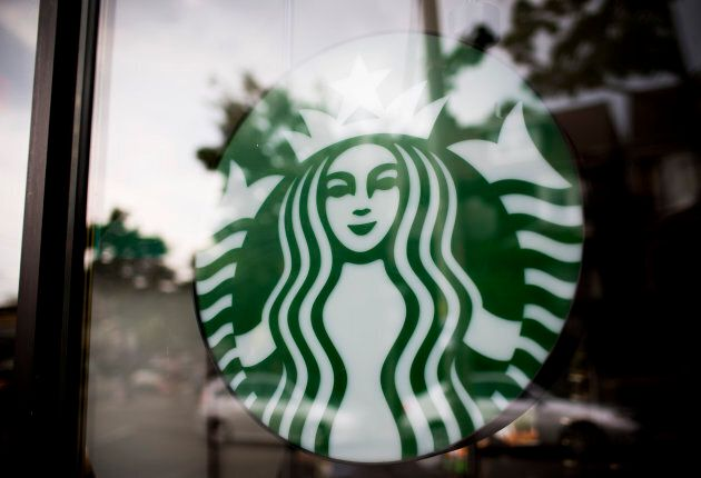 The Starbucks Corp. logo is displayed in the window of a store in Toronto, July 23,