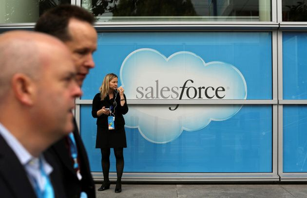 A woman stands near a Salesforce sign during the company's annual Dreamforce event, in San Francisco...