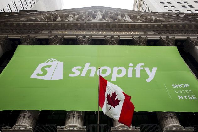 The logo of Shopify hangs behind the Canadian flag after the company's IPO at the New York Stock Exchange...