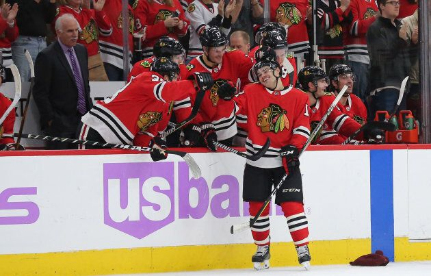 Chicago Blackhawks right wing Alex DeBrincat (12) is congratulated for scoring his third goal for a hat...