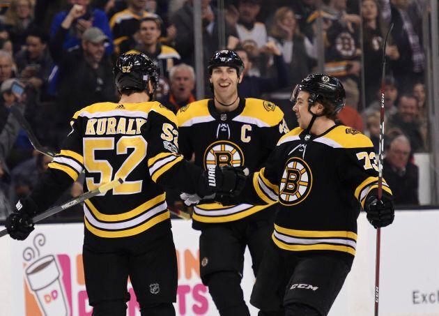 Boston Bruins center Sean Kuraly (52) reacts with defenseman Zdeno Chara (33) and defenseman Charlie...