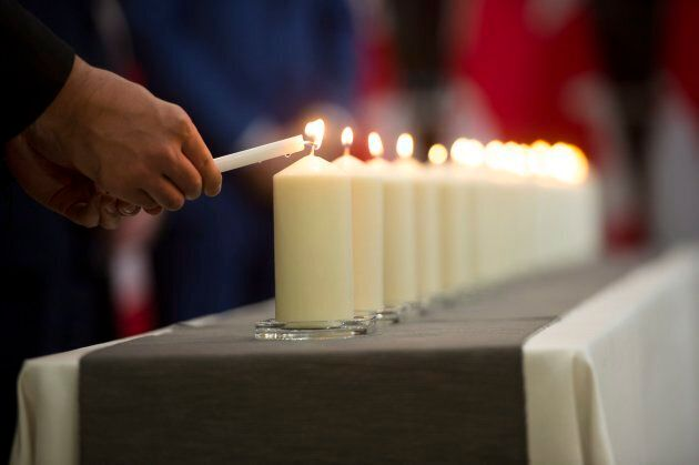 Liberal MP Shaun Chen lights a candle during a commemorative ceremony for the victims of Polytechnique at the Consulate General of Canada in Guangzhou, China on Dec. 6, 2017.
