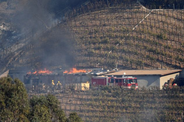 A building on the vineyard estate of media mogul Rupert Murdoch catches fire during the Skirball fire...