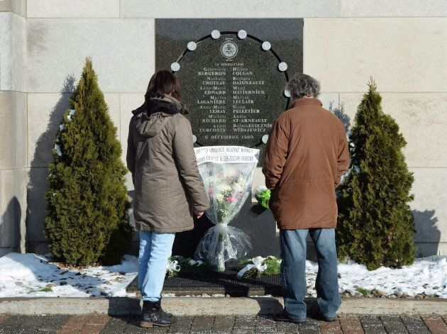 People look at the memorial plaque in honour of the 13 students and one staff member killed for the 27th...