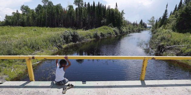 A boy from the Shoal Lake 40 First Nation sits on a bridge over a channel on June 25,