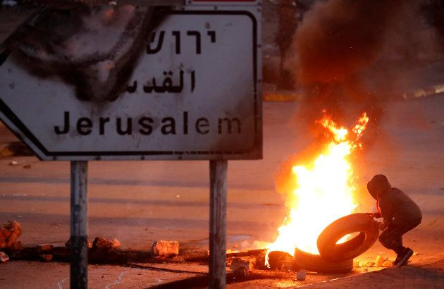 A Palestinian protester sets up a burning barricade near the West Bank city of Ramallah Dec. 8,