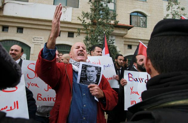 Around a hundred Palestinian protesters heckled and threw eggs at Canadian Foreign Minister John Baird...