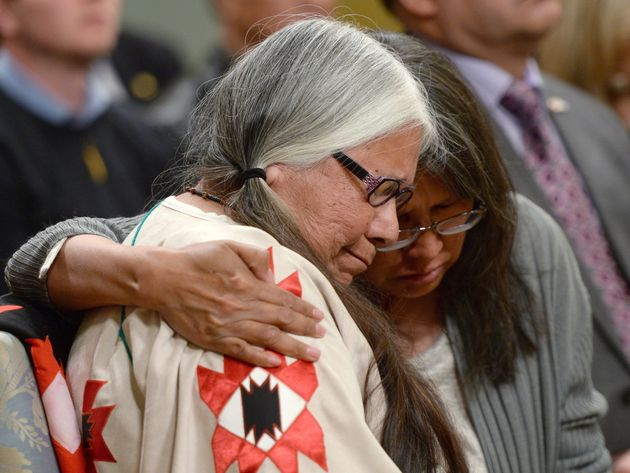 Residential school survivor Lorna Standingready is comforted by a fellow survivor in the audience during...