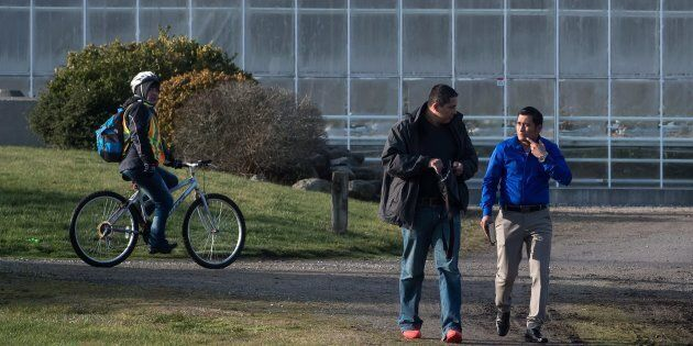 Workers leave a housing area at Windset Farms in Delta, B.C., on Dec. 10,
