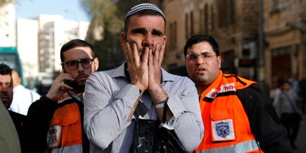 Israelis react at the scene of an attack at the Jerusalem Central Bus Station in Jerusalem on Dec. 10,