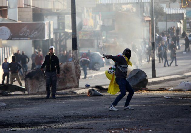 A Palestinian throws a rock with a slingshot in respond to Israeli security forces intervention in a...