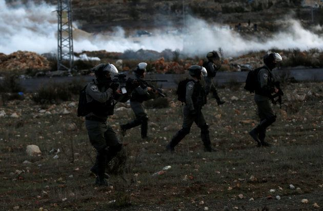An Israeli border policeman points his weapon during clashes with Palestinians at a protest against U.S....