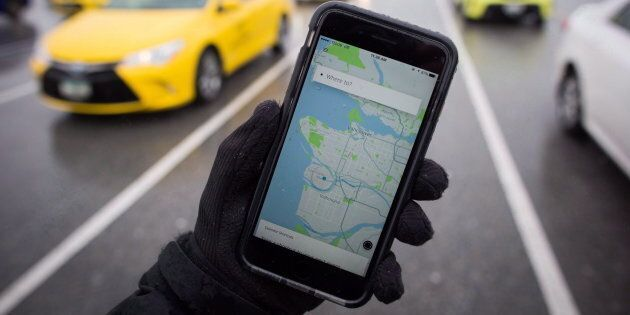 The Uber app is displayed on an iPhone as taxi drivers wait for passengers at Vancouver International...
