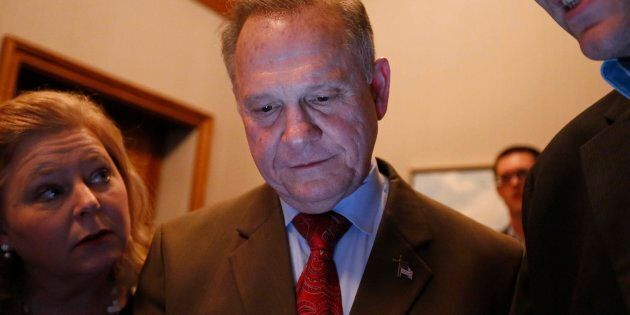 U.S. Senate candidate Roy Moore, centre, looks at election returns with staff during an election-night...