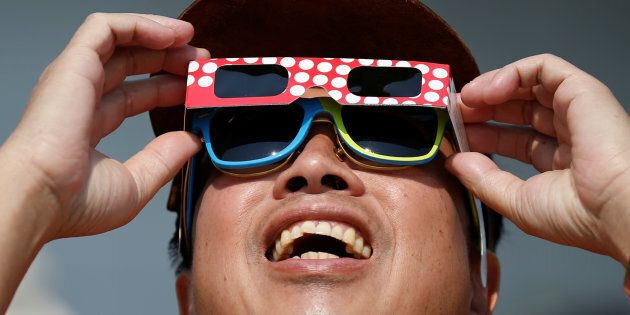 A man watches a partial solar eclipse at the Canada Aviation and Space Museum in Ottawa Aug. 21,